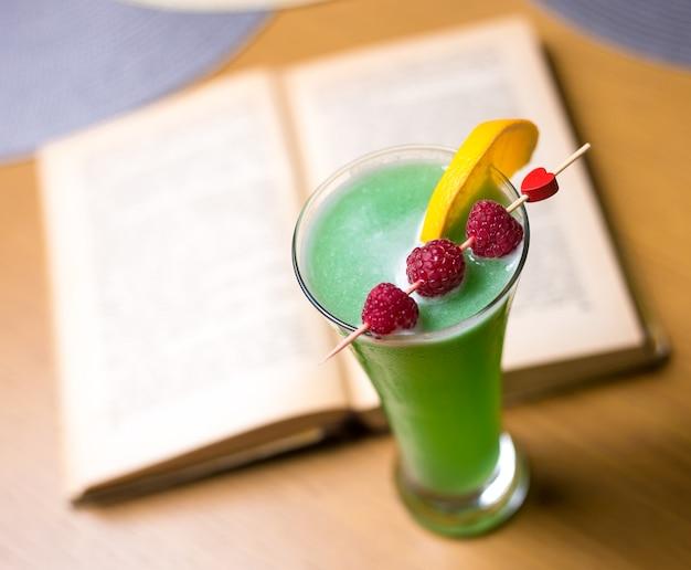 Vista laterale della calce dell'arancia del lampone dell'assenzio del liquore della bevanda di tequila del fatato verde del cocktail