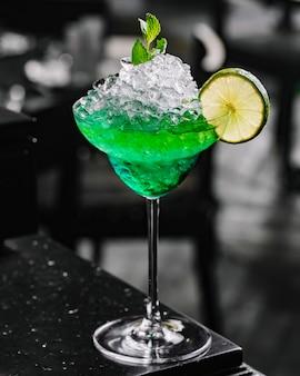 Vista laterale della calce dell'assenzio del liquore della vodka del tequila del fatato verde del cocktail