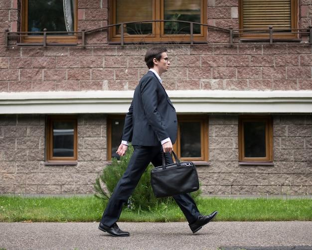 Vista laterale della camminata dell'uomo d'affari