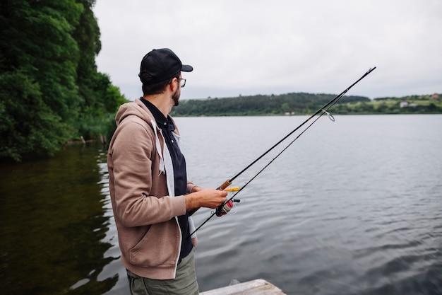 Vista laterale della canna da pesca della tenuta del giovane