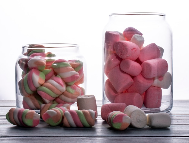 Vista laterale della caramella gommosa e molle torta colorata in barattolo di vetro su bianco