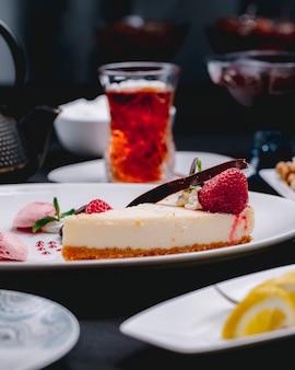 Vista laterale della cheesecake decorata con fragole fresche su un piatto bianco