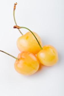 Vista laterale della ciliegia matura gialla isolata su bianco