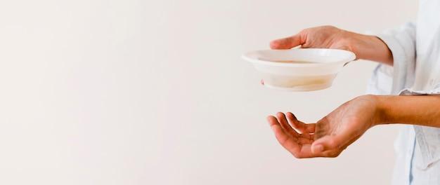 Vista laterale della ciotola della tenuta della persona di alimento con lo spazio della copia