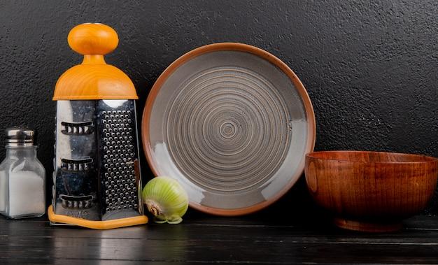 Vista laterale della cipolla bianca con sale, la grattugia, la ciotola e il piatto su superficie di legno e su fondo nero