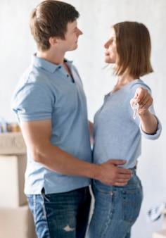 Vista laterale della coppia abbracciata che tiene le chiavi della nuova casa