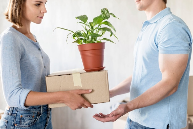 Vista laterale della coppia che maneggia scatole e pianta mentre si prepara a muoversi