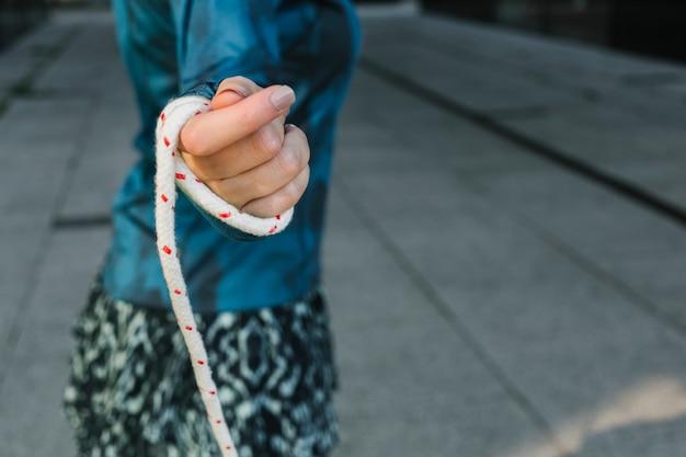 Vista laterale della corda di salto della tenuta della donna