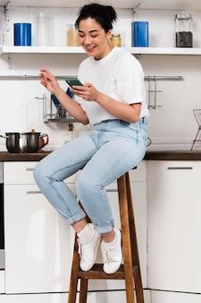 Vista laterale della donna a casa in cucina utilizzando smartphone