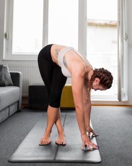 Vista laterale della donna a praticare yoga a casa concetto