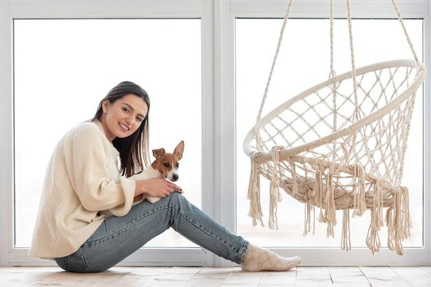 Vista laterale della donna accanto all'amaca che tiene il suo cane