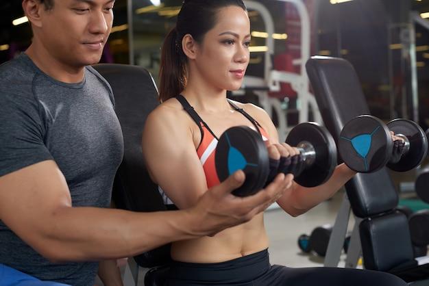 Vista laterale della donna adatta che risolve con il sollevamento pesi dell'istruttore personale