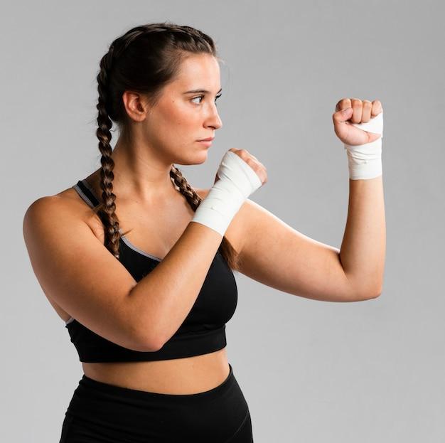 Vista laterale della donna adatta in posizione di combattimento