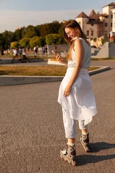 Vista laterale della donna all'aperto tenendo lo smartphone con le lame del rullo