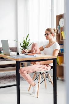 Vista laterale della donna allo scrittorio che funziona mentre a casa
