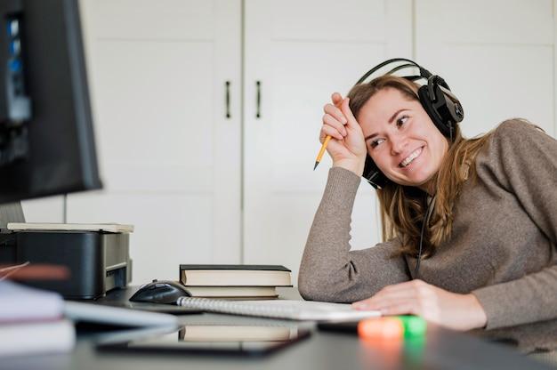 Vista laterale della donna allo scrittorio che ha una classe online