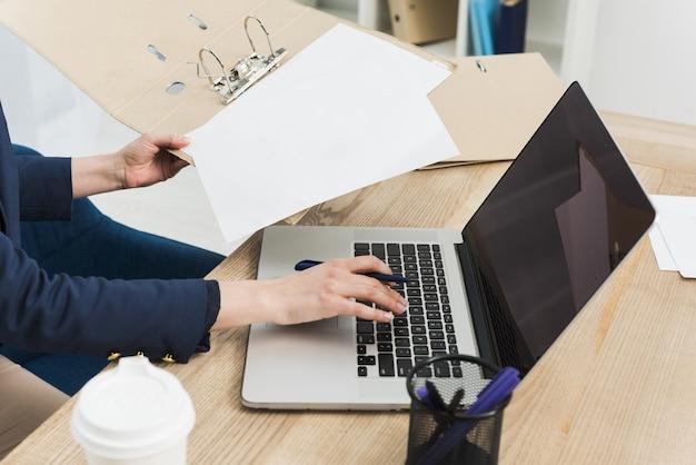 Vista laterale della donna allo scrittorio con il computer portatile e le carte