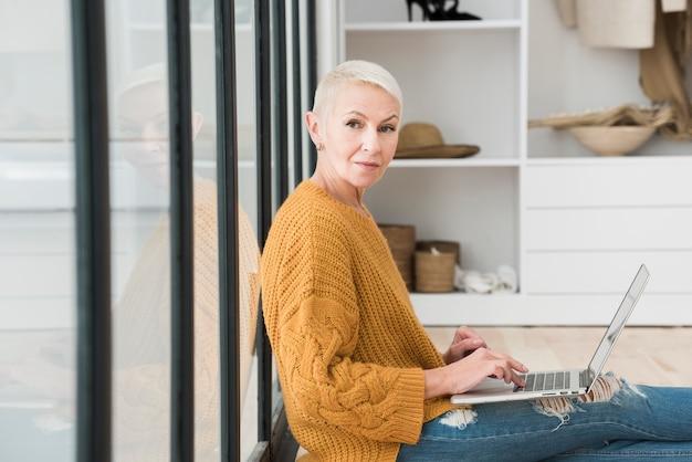 Vista laterale della donna anziana che lavora al computer portatile