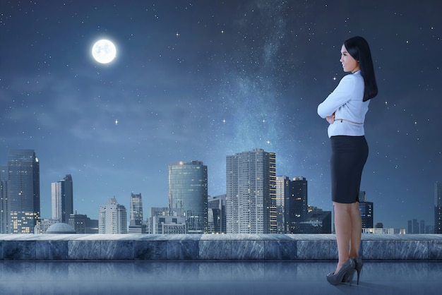 Vista laterale della donna asiatica di affari che sta sulla terrazza che guarda paesaggio urbano