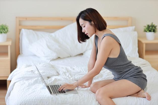 Vista laterale della donna asiatica indipendente adulta che lavora al computer e al telefono cellulare sul letto in camera da letto