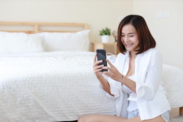 Vista laterale della donna asiatica indipendente adulta in camicia bianca che lavora al computer e al telefono cellulare in camera da letto con il fronte sorridente felice