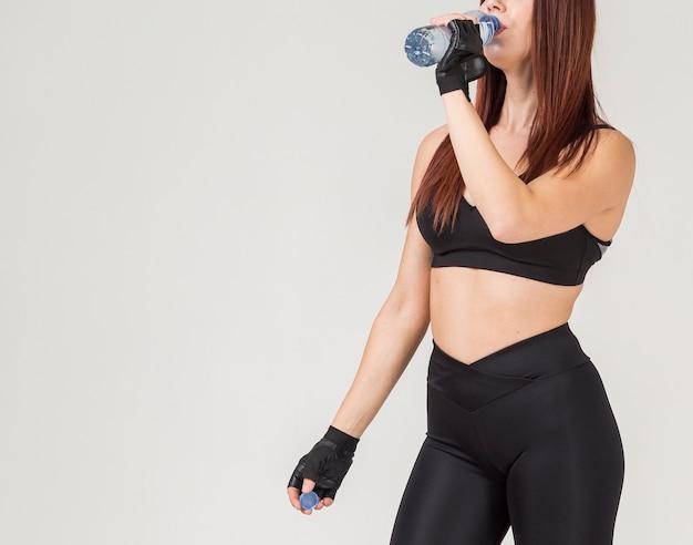 Vista laterale della donna atletica che beve da una bottiglia di acqua