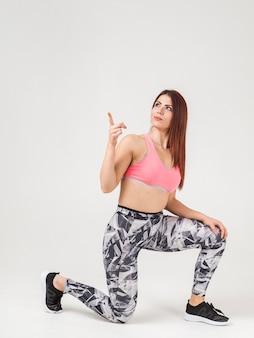 Vista laterale della donna atletica che indica in su