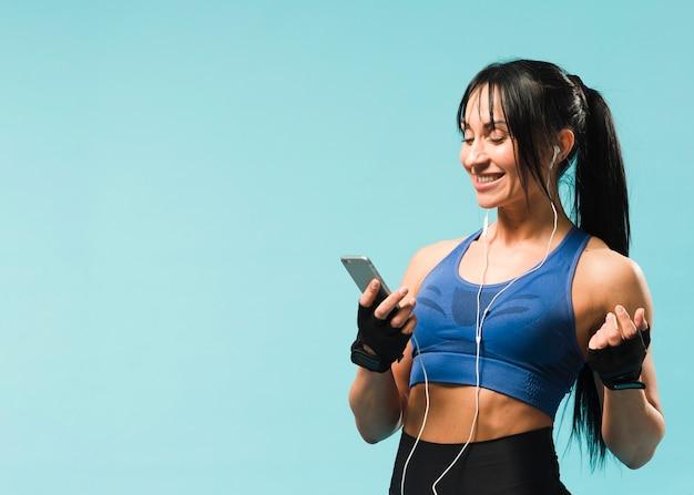 Vista laterale della donna atletica in attrezzatura della palestra che gode della musica