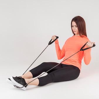Vista laterale della donna atletica utilizzando la fascia di resistenza