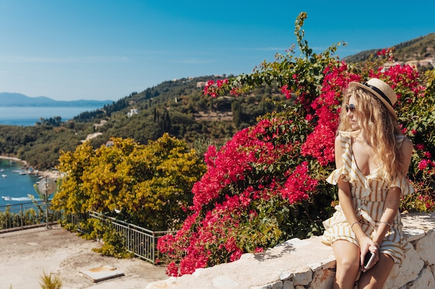 Vista laterale della donna bionda che esamina il paesaggio di mare stupefacente