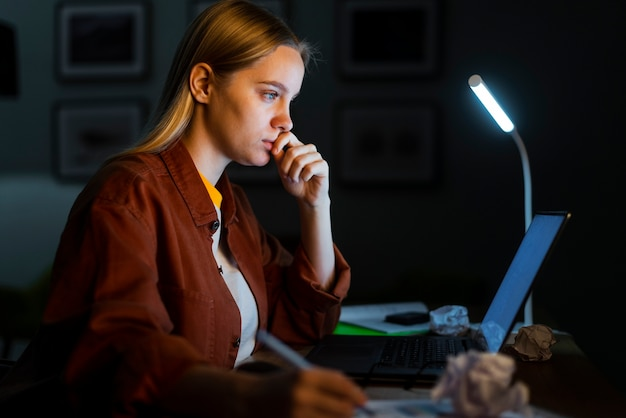 Vista laterale della donna bionda che lavora al computer portatile