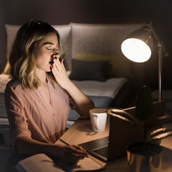 Vista laterale della donna bionda che lavora fino a tardi