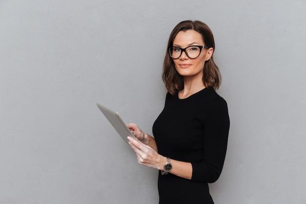Vista laterale della donna calma di affari che per mezzo del computer della compressa