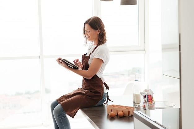 Vista laterale della donna casuale in grembiule che si siede sulla tavola e che per mezzo del computer della compressa