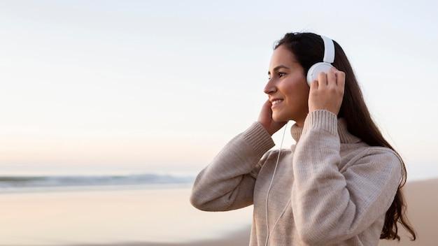 Vista laterale della donna che ascolta la musica in cuffia all'aperto