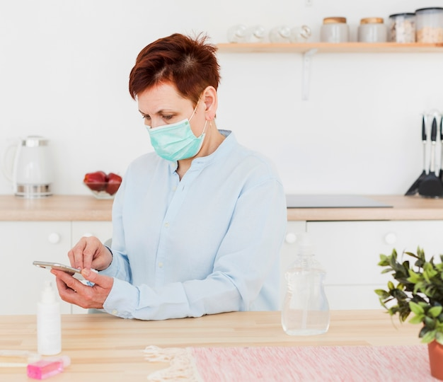 Vista laterale della donna che disinfetta il suo telefono mentre indossando maschera medica