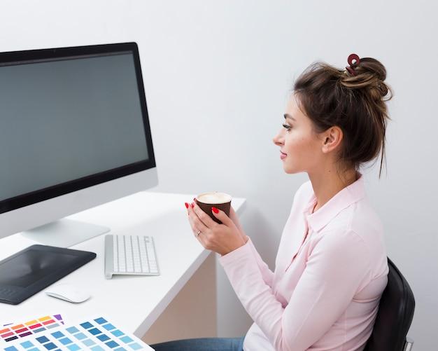 Vista laterale della donna che esamina computer mentre tenendo tazza di caffè
