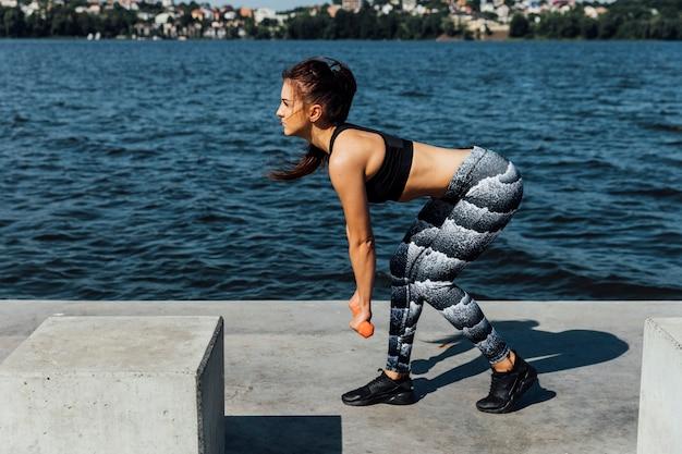 Vista laterale della donna che fa allenamento con i pesi