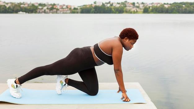Vista laterale della donna che fa esercizio sulla spiaggia