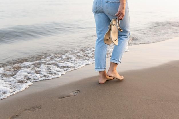 Vista laterale della donna che fa una passeggiata sulla spiaggia
