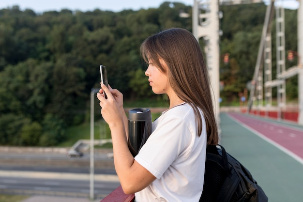Vista laterale della donna che fotografa la vista mentre viaggia da solo