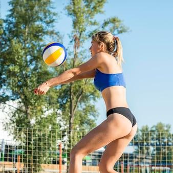 Vista laterale della donna che gioca a pallavolo sulla spiaggia
