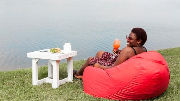 Vista laterale della donna che gode del cocktail sul sacchetto di fagioli all'aperto
