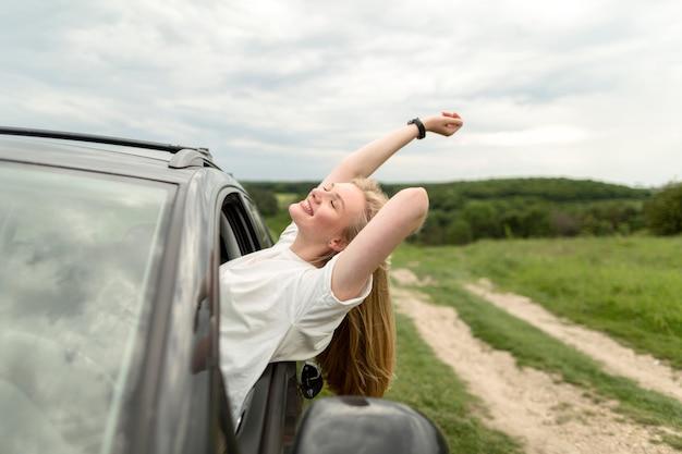 Vista laterale della donna che gode di un giro in auto