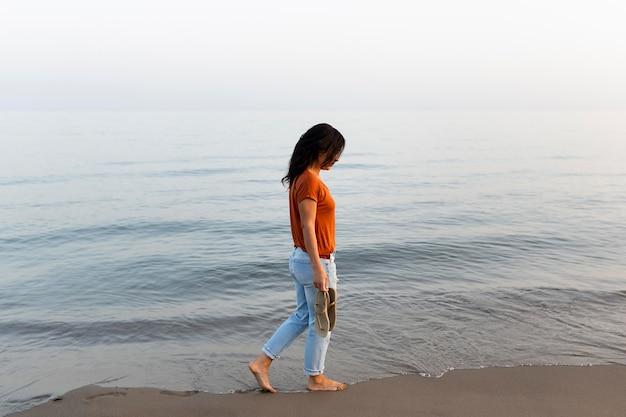 Vista laterale della donna che gode di una passeggiata sulla spiaggia