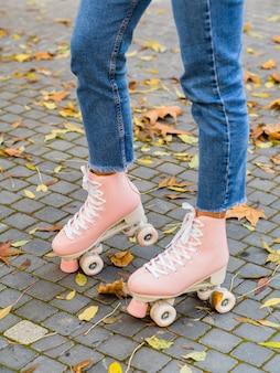 Vista laterale della donna che indossa jeans con pattini a rotelle