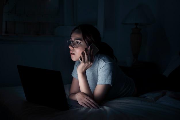 Vista laterale della donna che lavora fino a tardi mentre parla al telefono