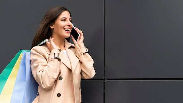 Vista laterale della donna che parla sullo smartphone mentre si tengono le borse della spesa
