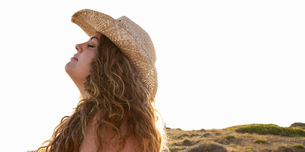Vista laterale della donna che posa all'aperto al sole con il cappello