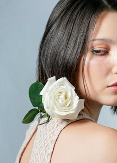 Vista laterale della donna che posa con la rosa bianca